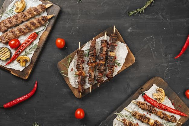 Gegrilde lula-kebab op spiesjes geserveerd op een houten bord, zwarte tafel achtergrond