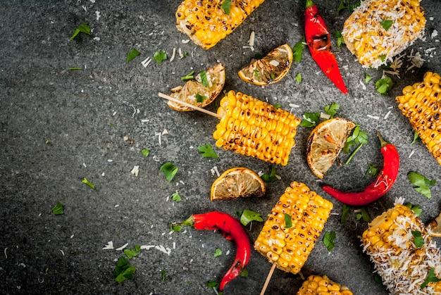 Gegrilde maïs met een sprenkel van kaas, hete chili peper en citroen op een donkere stenen tafel.