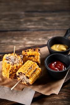 Gegrilde maïs met sauzen op een houten ruimte. traditioneel amerikaans bijgerecht