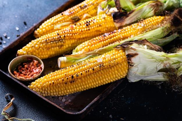 Gegrilde maïskolf met zout, paprika en boter