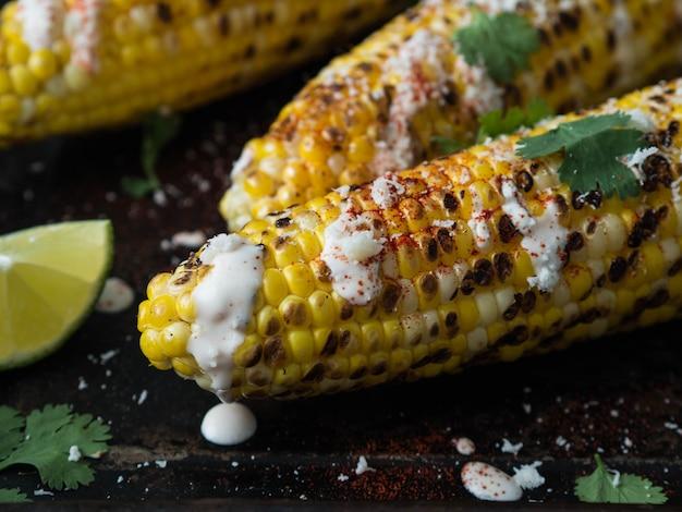 Gegrilde maïskolven met saus, koriander, limoen, paprika en kaas.