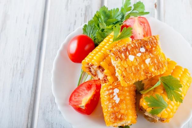 Gegrilde maïskolven met solt, specerijen en tomaten