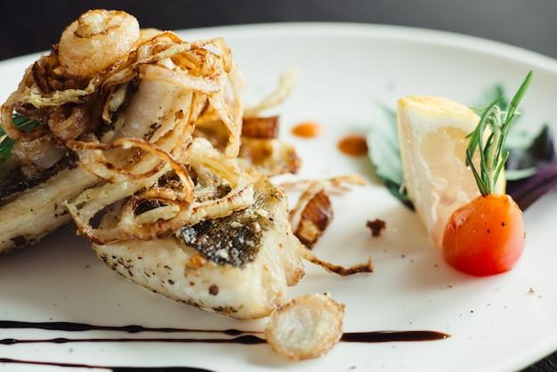 Gegrilde makreel met ui op witte plaat op houten tafel