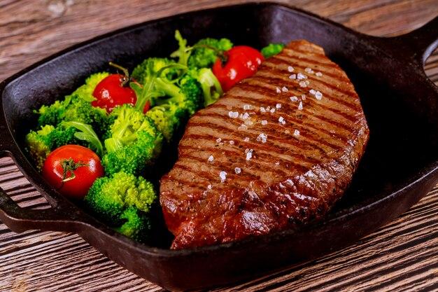 Gegrilde medium zeldzame biefstuk met broccoli en tomaat op de grillpan.