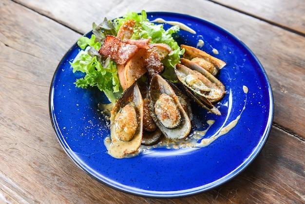 Gegrilde mosselschelp ham groenten en saus zeevruchten geserveerd op tafel