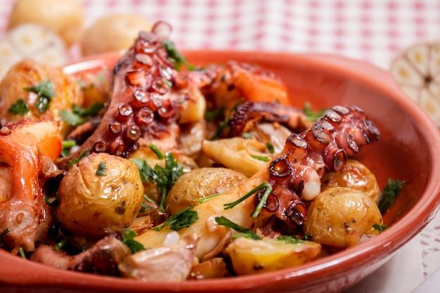 Gegrilde ocotpus met aardappelen, knoflook en salsa.