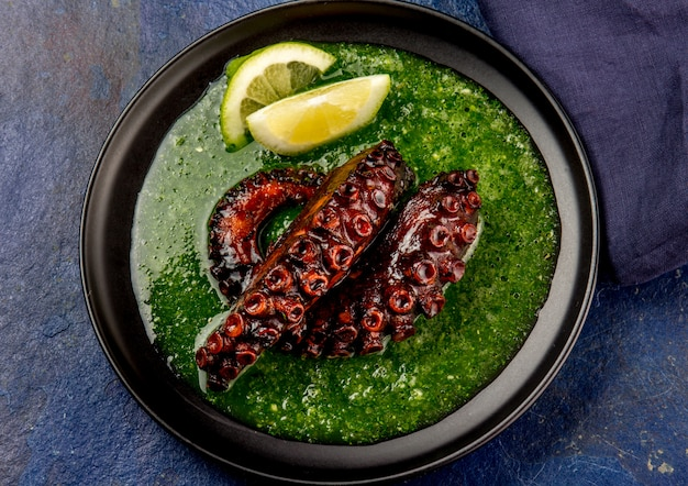 Gegrilde octopus serveert met grijnsaus op zwarte plaat