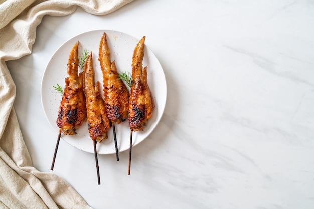 Gegrilde of barbecue kippenvleugelspies op plaat