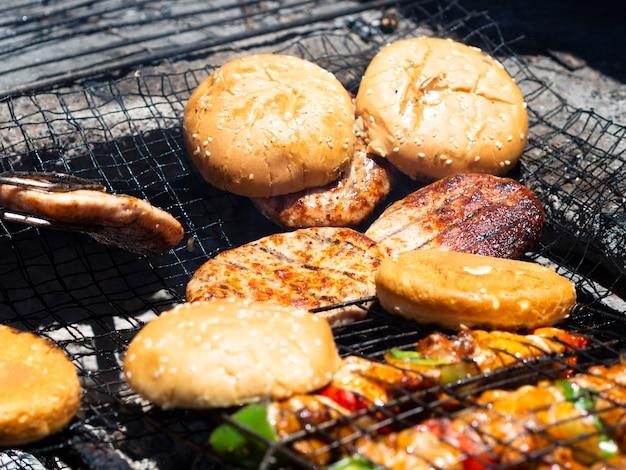 Gegrilde pasteitjes en hamburgerbroodjes bij de grill