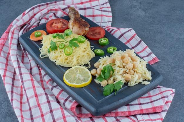 Gegrilde poot, spaghetti en rijst op donker bord.