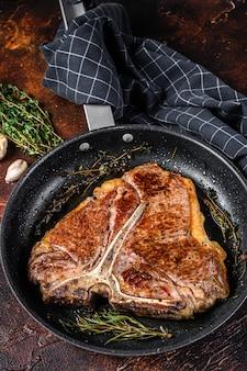 Gegrilde porterhouse rundvlees steak met kruiden in een pan. donkere achtergrond. bovenaanzicht.
