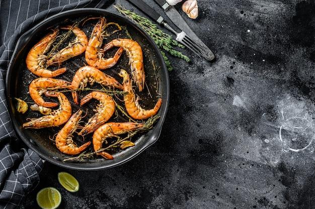 Gegrilde reuzengarnalen, garnalen met knoflook, citroen, kruiden in de pan. zwart oppervlak. bovenaanzicht. kopieer ruimte