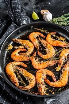 Gegrilde reuzengarnalen, garnalen met knoflook, citroen, kruiden in de pan. zwart oppervlak. bovenaanzicht