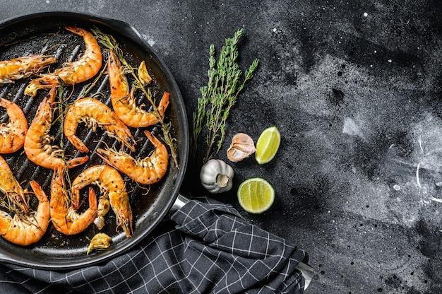 Gegrilde reuzengarnalen, garnalen met knoflook, citroen, kruiden in de pan. zwarte achtergrond