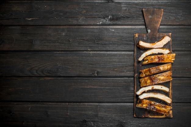 Gegrilde ribben gesneden op een oud bord op houten tafel.
