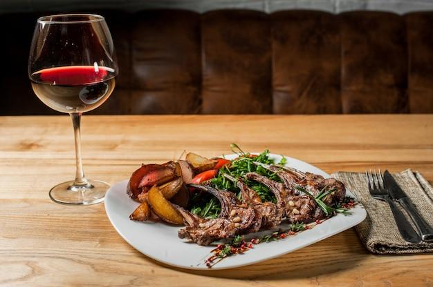 Gegrilde ribben met groenten in een witte plaat en rode wijnglas