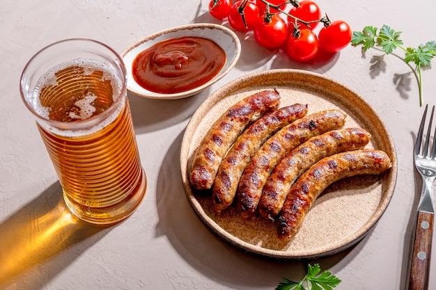 Gegrilde rundergehakt en varkensworst met barbecuesaus op een bord en een glas bier op tafel, foto met trending hard zonlicht en schaduwen.