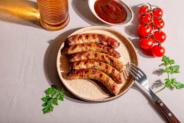 Gegrilde rundergehakt en varkensworst met barbecuesaus op een bord en een glas bier
