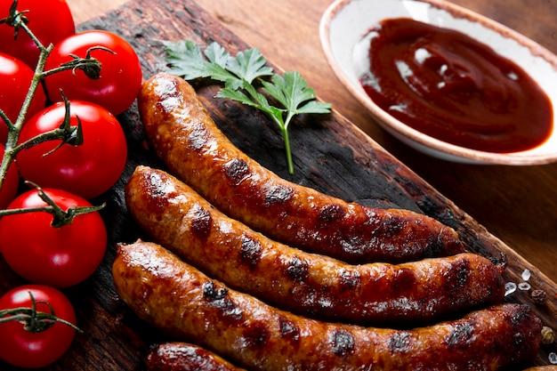 Gegrilde rundergehakt en varkensworst met barbecuesaus op een houten bord close-up.