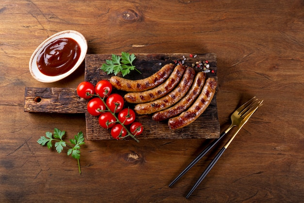 Gegrilde rundergehakt en varkensworst met barbecuesaus op houten snijplank bovenaanzicht.