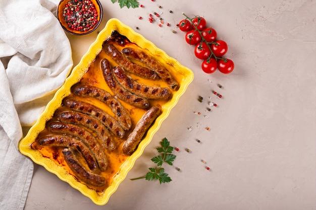 Gegrilde rundergehakt en varkensworstjes op gele ovenschaal bovenaanzicht, vrije ruimte voor tekst.