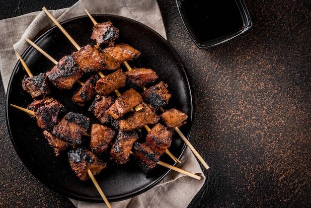 Gegrilde runderlever op spiesjes, met teriyaki of sojasaus, yakitori, donker roestig tafelblad