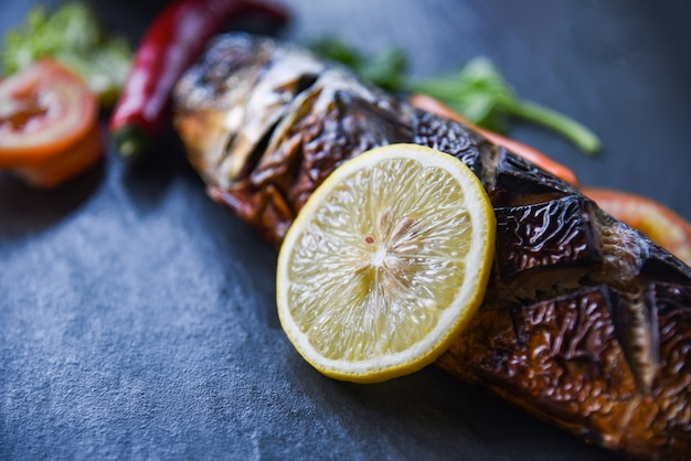 Gegrilde saba vis met zoete saus en citroenkruiden met donkere achtergrond