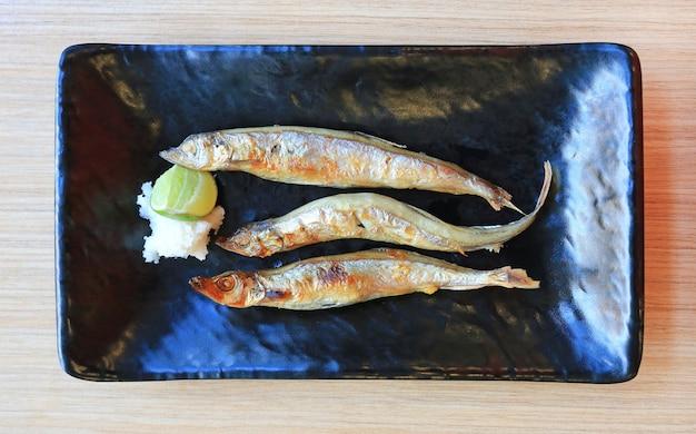 Gegrilde shishamo geserveerd met citroen en ui, japans eten.