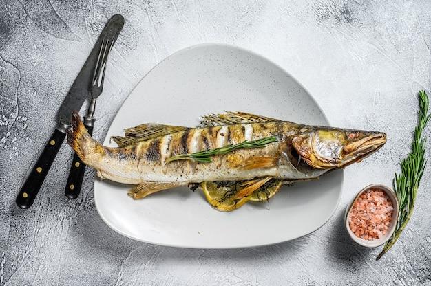 Gegrilde snoekbaars, snoekbaars vis met kruiden en citroen op een bord. grijze houten achtergrond. bovenaanzicht.