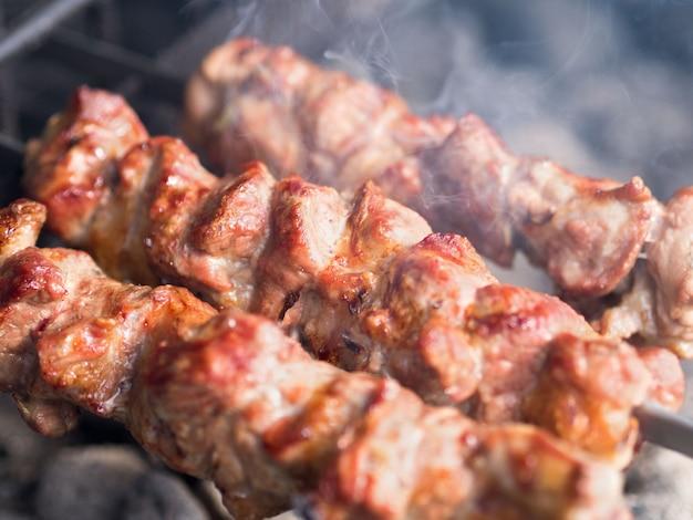 Gegrilde spiesen van vlees op de kolen, met rook. het straatvoedsel.