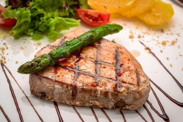 Gegrilde steak en asperges op een bord in een restaurant