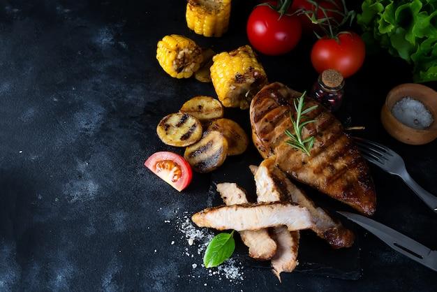 Gegrilde steak en groente, gebakken aardappelen en groene salade op donker