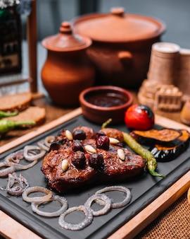 Gegrilde steak in kersensaus met uienpeper aardappel aubergine zijaanzicht