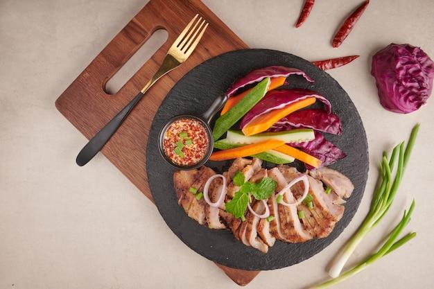 Gegrilde steak met gemengde groenten en kruiden. zelfgemaakt lekker eten. stenen oppervlak. varkenslapje vlees met salade. gegrild varkensvlees is een van de meest populaire thaise gerechten. gegrild varkensvlees met pittige dip.