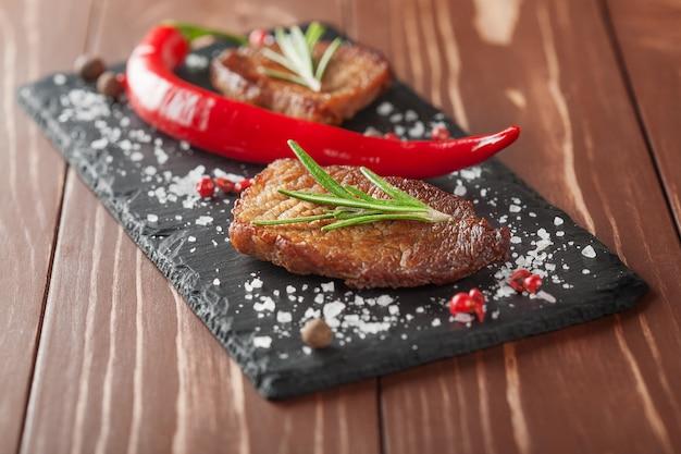 Gegrilde steak met rozemarijn en chili pepers op houten achtergrond