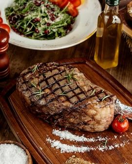 Gegrilde steak met zoute kruiden en gegrilde tomaat geserveerd op een houten bord