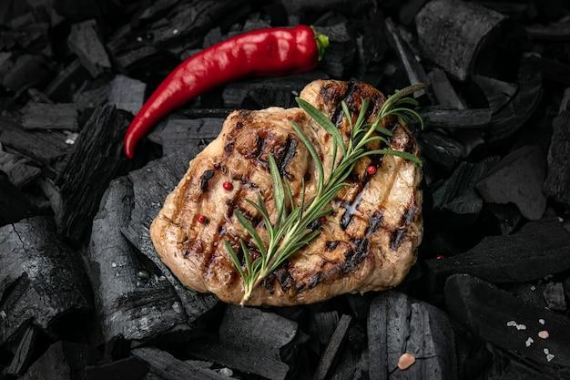 Gegrilde steak op een achtergrond van zwarte houtskool