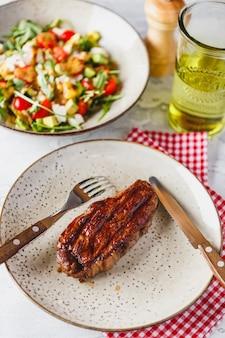 Gegrilde steaks en groentesalade op licht.