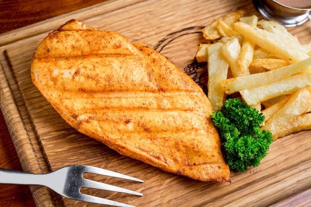 Gegrilde steaks, gebakken aardappelen en groenten