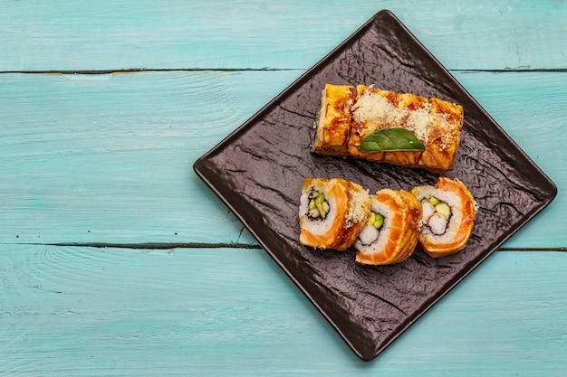 Gegrilde sushi met tijgergarnalen. japans of koreaans broodje met verschillende verse ingrediënten. trendy turquoise achtergrond
