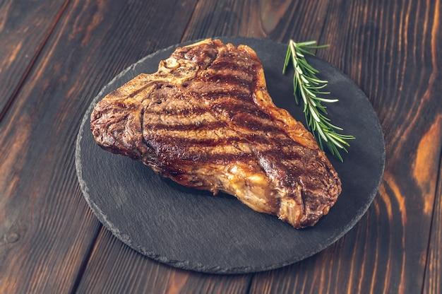 Gegrilde t-bone steak met verse rozemarijn op het stenen bord