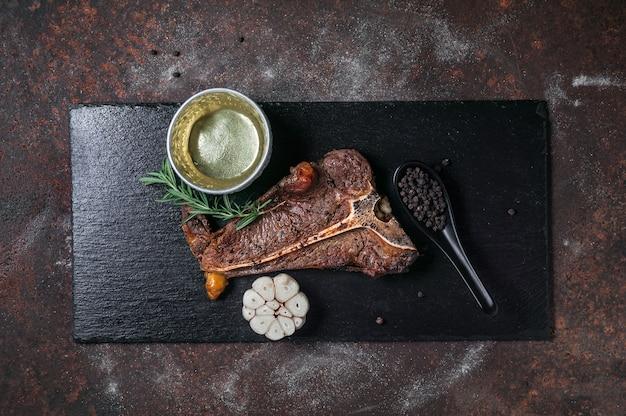 Gegrilde t - bone steak op zwarte leiplaat en oude keukentafel