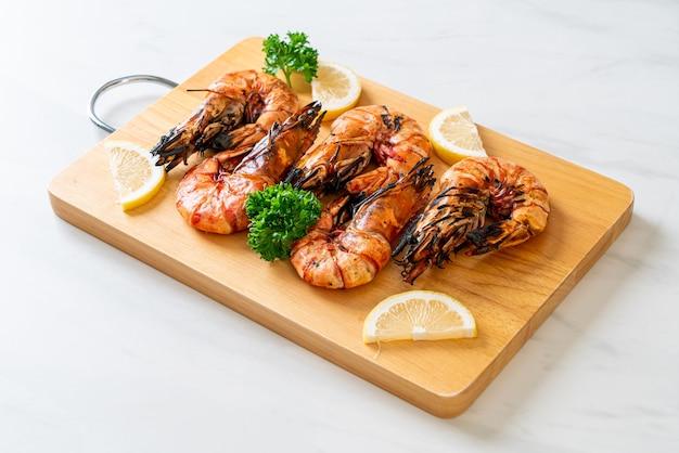 Gegrilde tijgergarnalen of garnalen met citroen op een houten bord