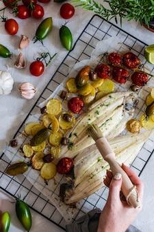 Gegrilde tongvis met groene en rode kersentomaten, aardappel, kappertjes, knoflook, peterselie en olijfolie