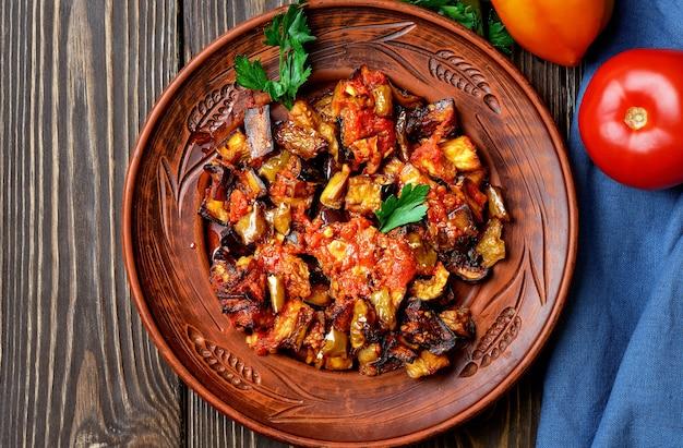 Gegrilde turkse aubergines in tomatensaus (soslu patlican of saksuka.). een lekker en eenvoudig turks gerecht of aperitief voor hoofdgerechten. lay-out op donkere houten