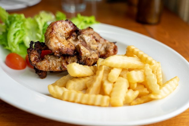 Gegrilde varkens- en friet, gerangschikt op een mooie witte schotel met salade