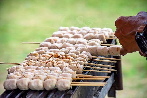 Gegrilde varkensgehaktballetjes op de grill, houtskool staat in brand.