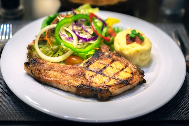 Gegrilde varkenskoteletten en groentesalade. biefstuk op plaat.