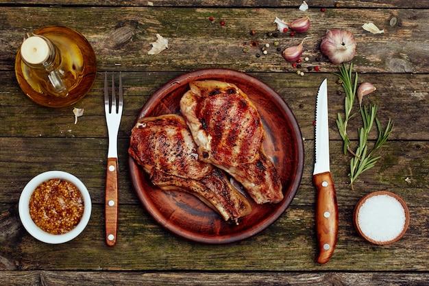 Gegrilde varkenskoteletten in een plaat met vork en mes op een oude houten tafel.