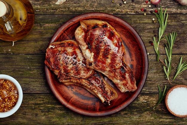 Gegrilde varkenskoteletten in een plaat op een oude houten tafel.